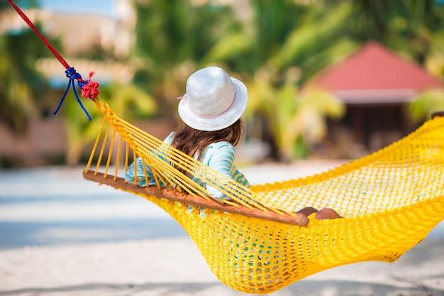 Hermosa chica relajante en hamaca en playa blanca Foto Premium