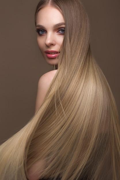Hermosa chica rubia con un cabello perfectamente liso, maquillaje clásico, cara de belleza Foto Premium