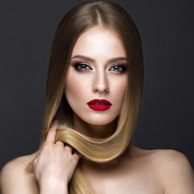 Hermosa chica rubia con un cabello perfectamente liso, maquillaje clásico y labios rojos. cara de belleza Foto Premium