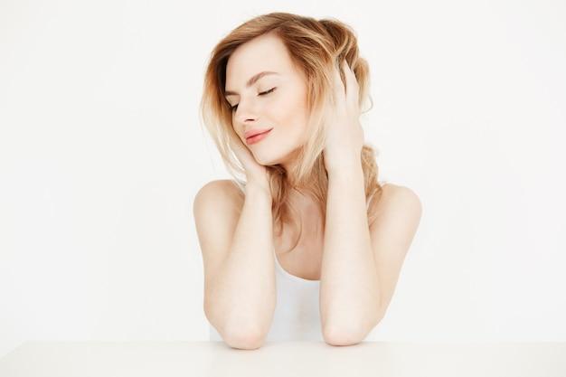 Hermosa chica rubia con la piel limpia y fresca sentada en la mesa tocando el pelo sonriendo. cuidado de la piel belleza y spa. ojos cerrados. Foto gratis