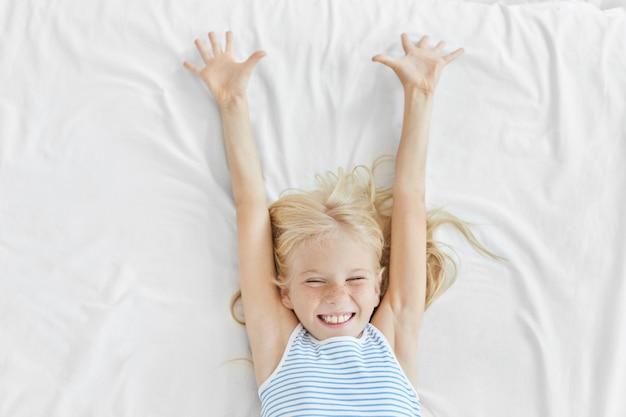 Hermosa chica rubia con piel sana y pecosa, cerrando los ojos con placer y estirándose en una cama blanca, regocijándose al comenzar un nuevo día Foto gratis