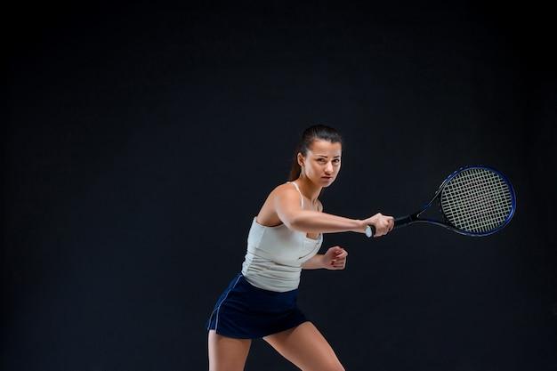Hermosa chica tenista con una raqueta sobre fondo oscuro Foto gratis