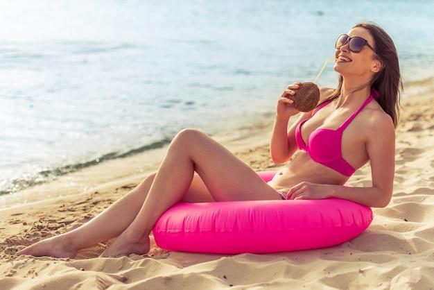 Hermosa chica en traje de baño rosa está bebiendo leche de coco. Foto Premium