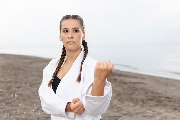 Hermosa chica en traje de karate al aire libre Foto gratis