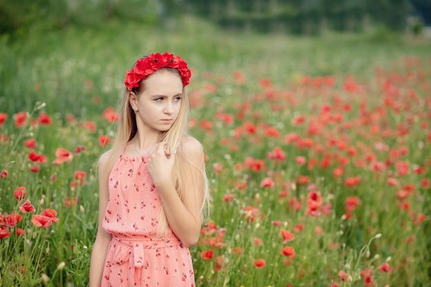 Hermosa chica ucraniana en campo de amapolas y trigo. Foto Premium