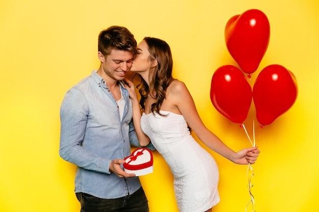 Hermosa chica vestida de blanco con globos rojos besando a su novio Foto gratis
