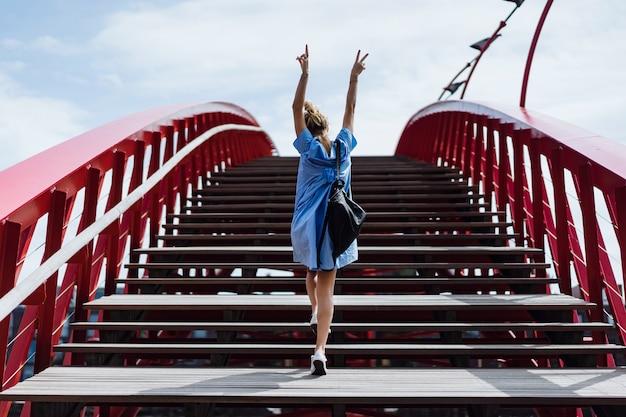 Hermosa chica en un vestido azul posando en el puente Foto gratis