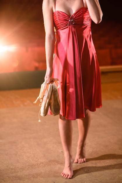 Hermosa chica en un vestido rojo bailando en el escenario. Foto Premium