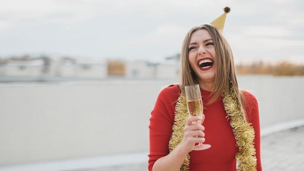 Hermosa chica en vestido rojo riendo en la azotea con copa de champán Foto gratis
