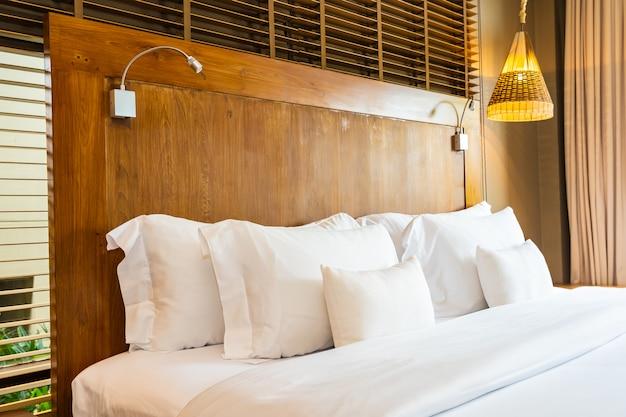 Hermosa y cómoda almohada blanca de lujo en la cama y decoración de mantas en el dormitorio Foto gratis