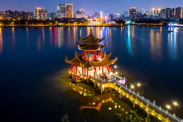 Hermosa decorada pagoda china tradicional con la ciudad de kaohsiung en segundo plano en la noche Foto Premium