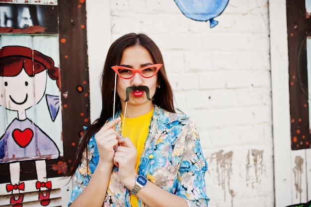 Hermosa diversión adolescente con gafas y bigote en palo llevar camiseta amarilla, cerca de la pared de graffiti. Foto Premium