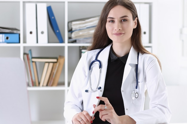Hermosa doctora sonriente espera portapapeles Foto Premium