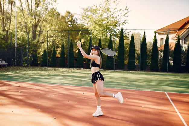 Hermosa y elegante chica en la cancha de tenis Foto gratis
