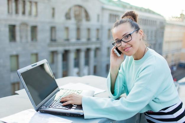 Hermosa y elegante chica trabaja para una laptop. Foto Premium