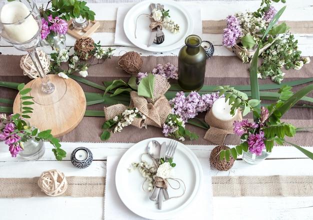 Hermosa y elegante mesa decorada para vacaciones: boda o día de san valentín con cubiertos modernos, arco, vidrio, velas y regalos. Foto gratis