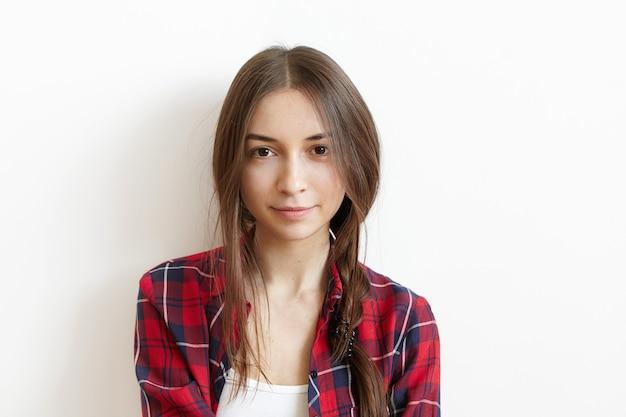 Hermosa y encantadora mujer caucásica joven con ojos marrones y cabello oscuro desordenado Foto gratis