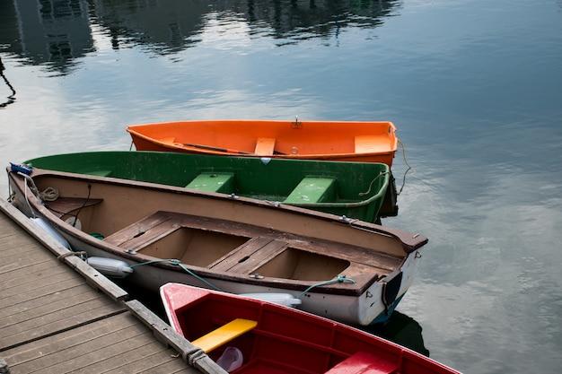 Hermosa escena de cuatro coloridas embarcaciones junto a la orilla de madera del lago Foto gratis