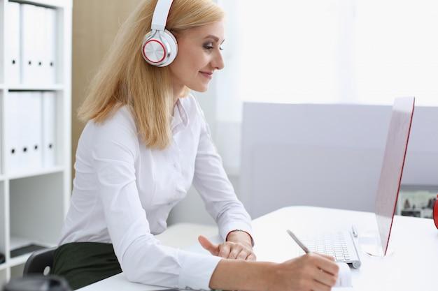 Hermosa estudiante con auriculares escuchando música y aprendiendo. sostenga el bolígrafo en la mano y mire el monitor de la computadora portátil Foto Premium