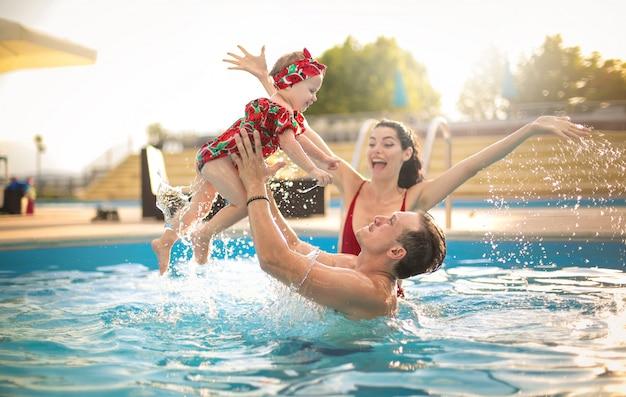 Hermosa familia divirtiéndose en una piscina Foto Premium