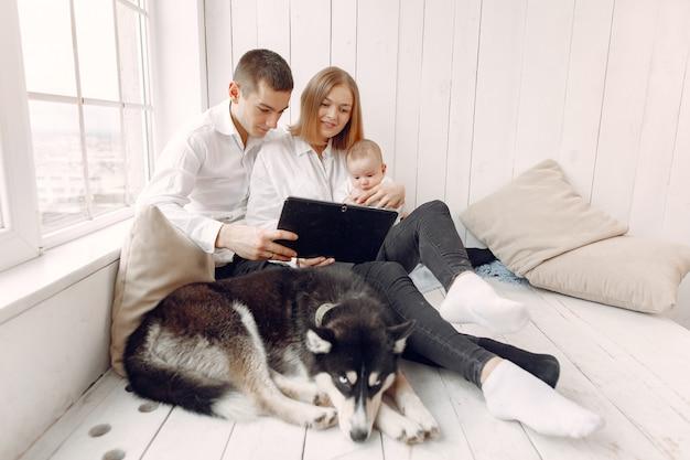 Hermosa familia pasar tiempo en una habitación con una tableta Foto gratis