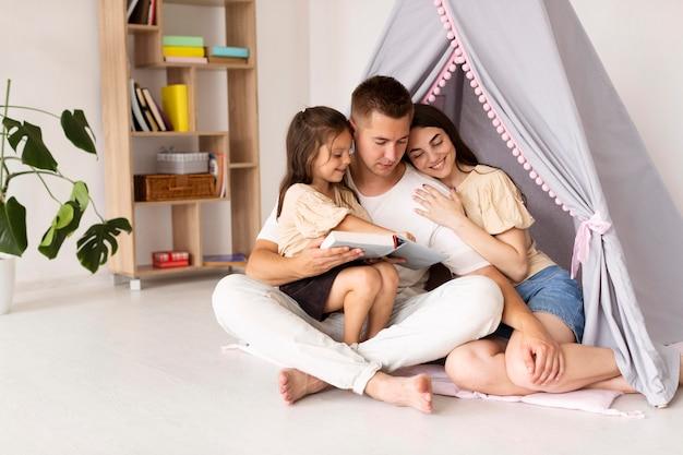Hermosa familia de tiro largo pasar tiempo juntos en casa con espacio de copia Foto gratis
