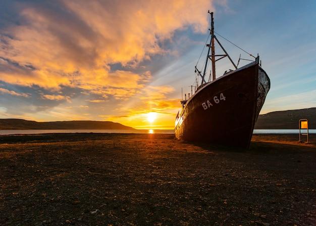 Una hermosa foto de un barco de pesca acercándose a la playa al amanecer. Foto gratis