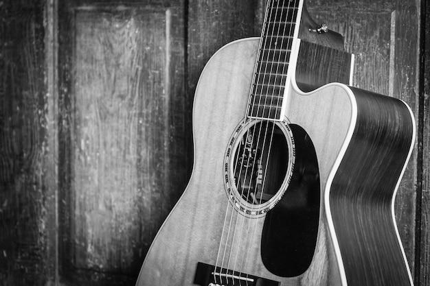Hermosa foto en escala de grises de una guitarra acústica apoyada en una puerta de madera sobre una superficie de madera Foto gratis