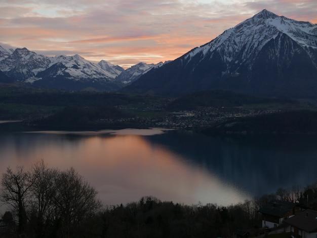 Hermosa foto de una montaña empinada con nieve blanca en la cima con un paisaje de puesta de sol en el cielo Foto gratis