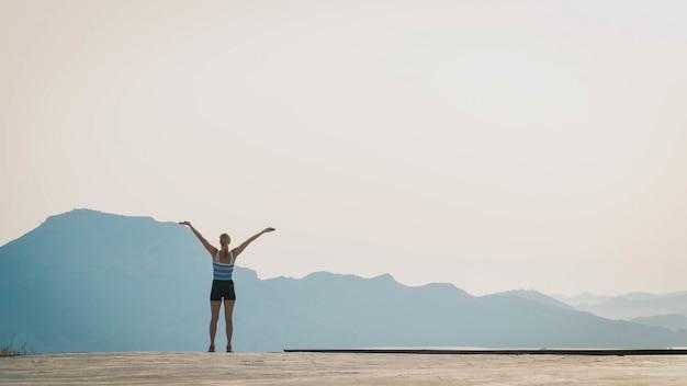 Hermosa foto de una mujer de pie en el suelo con las siluetas de las colinas en el fondo Foto gratis