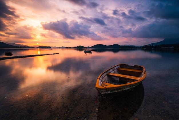 Hermosa foto de un pequeño lago con un bote de remos de madera en foco y nubes impresionantes en el cielo Foto gratis