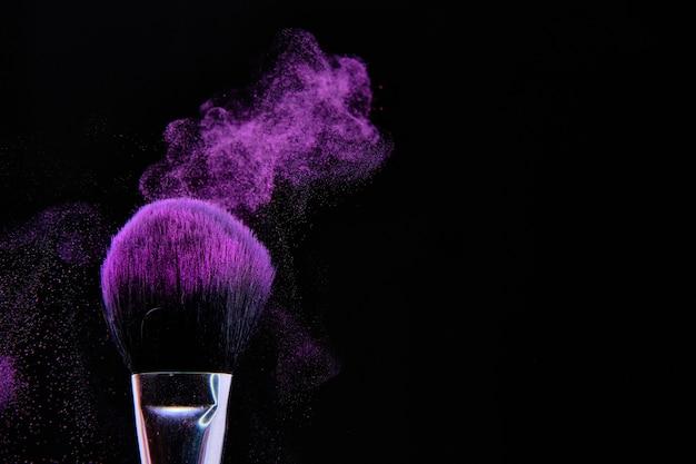 Hermosa foto de pincel de maquillaje aislado en negro Foto gratis