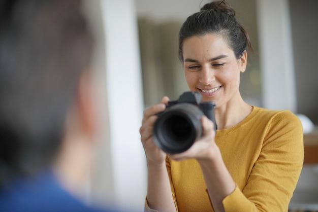 Hermosa fotógrafa profesional tomando fotos de una modelo. Foto Premium