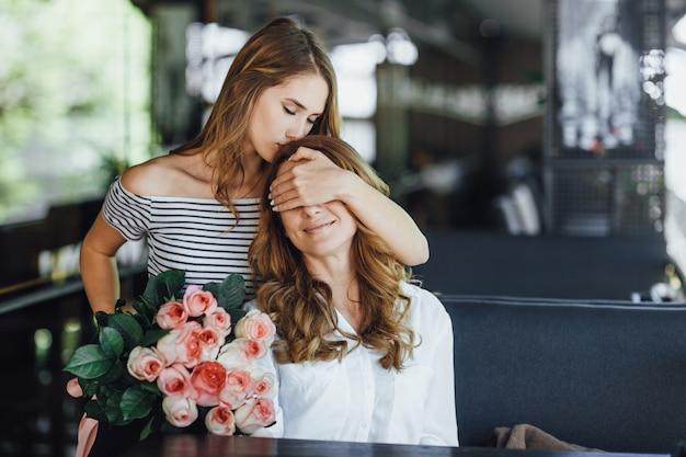Hermosa hija adolescente cierra los ojos de su madre y le da un ramo de rosas Foto Premium