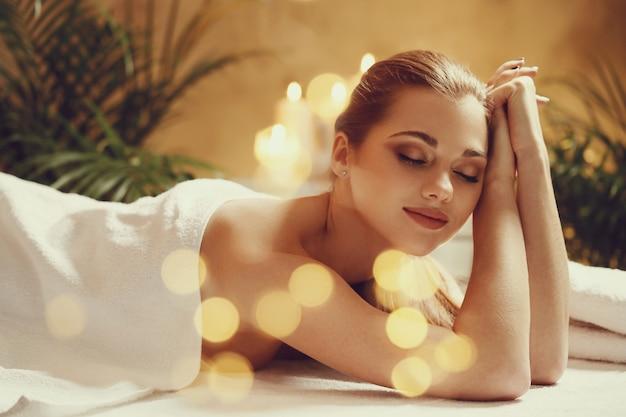 Hermosa joven acostada y esperando su masaje. concepto de spa Foto gratis
