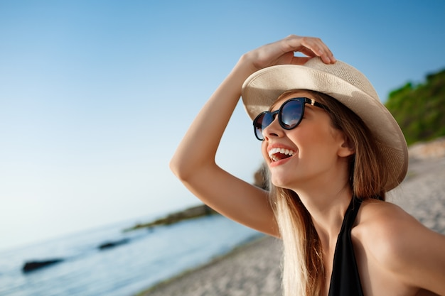 Hermosa joven alegre en sombrero y gafas de sol descansa en la playa de la mañana Foto gratis