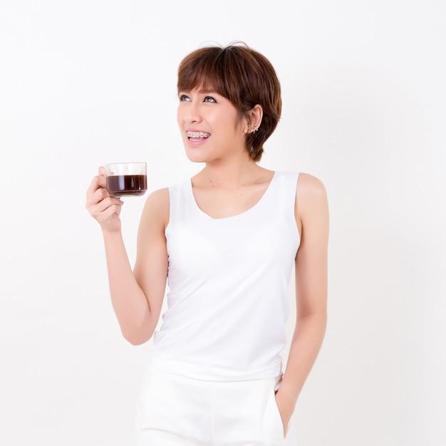 Hermosa joven asiática con una taza de café caliente. Foto Premium