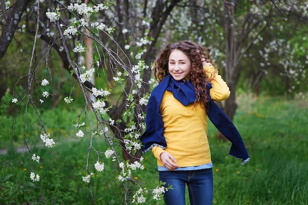 Hermosa joven caminando en un jardín floreciente Foto Premium