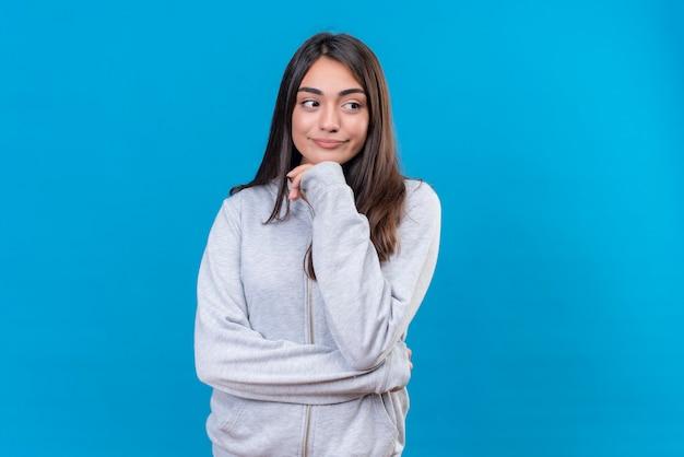 Hermosa joven con capucha gris mirando a otro lado con mirada pensativa Foto gratis
