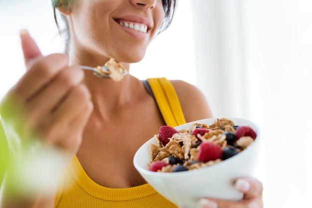 Hermosa joven comiendo cereales y frutas en casa. Foto gratis