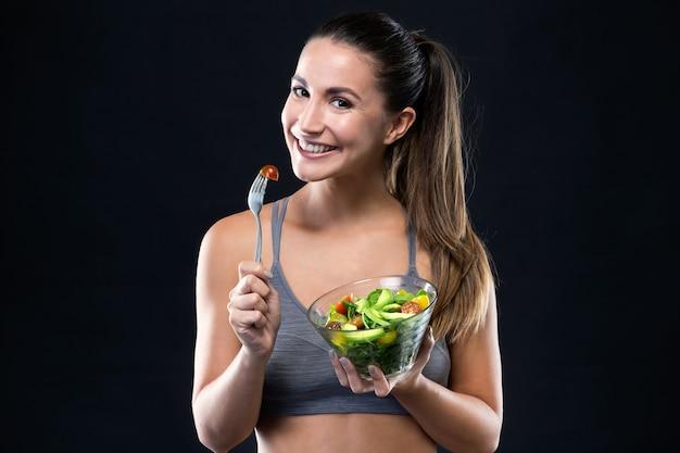 Hermosa joven comiendo ensalada sobre fondo negro. Foto gratis