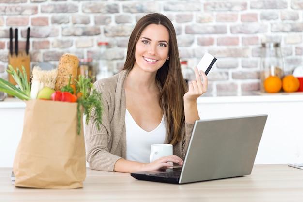 Hermosa joven de compras con su tarjeta en línea en la cocina. Foto gratis