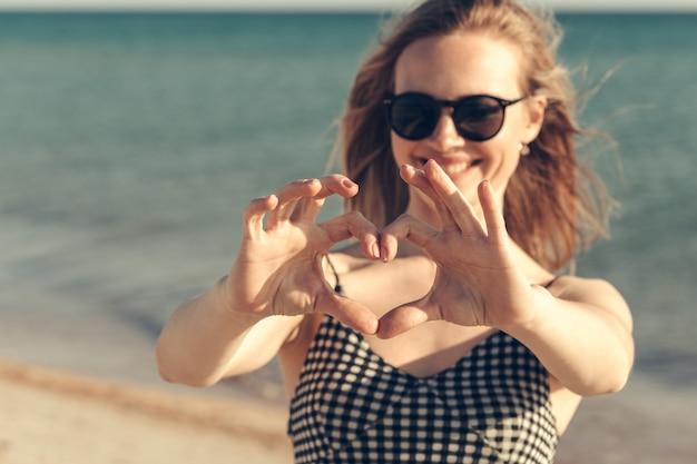 Hermosa joven disfruta de las vacaciones de verano en la playa Foto Premium