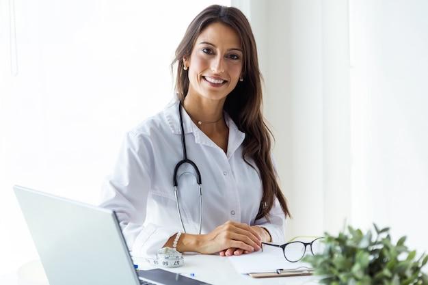 Hermosa joven doctora mirando a la cámara en la oficina. Foto gratis