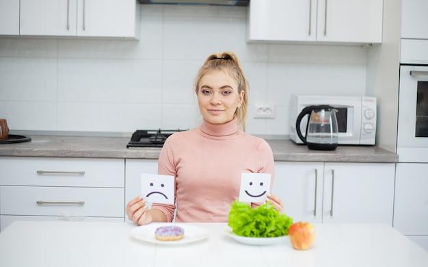 Hermosa joven eligiendo entre comida sana y comida chatarra Foto Premium