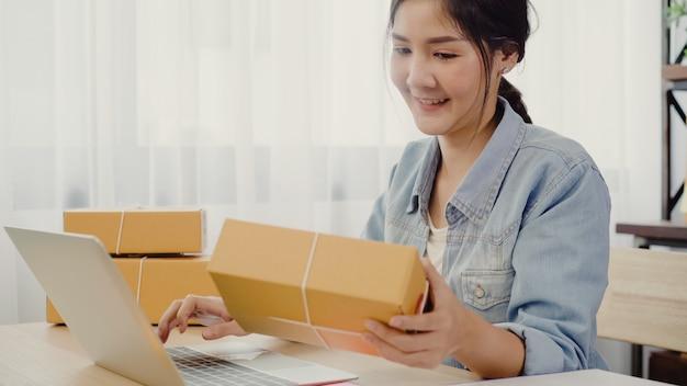 Hermosa joven empresaria asiática inteligente, dueña de una mujer de negocios en línea que comprueba el producto. Foto gratis