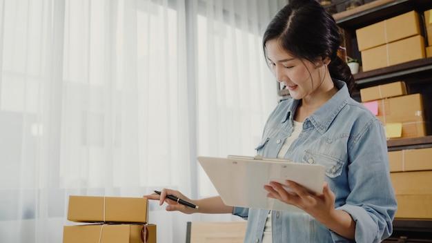 Hermosa joven empresaria asiática inteligente, dueña de una mujer de negocios que comprueba su producto en stock Foto gratis