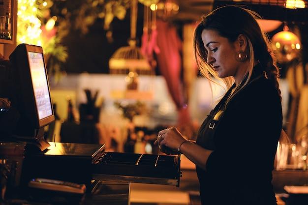 Una hermosa joven en el escritorio en un restaurante Foto Premium