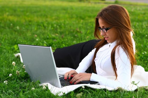 Hermosa joven estudiando en el parque Foto gratis