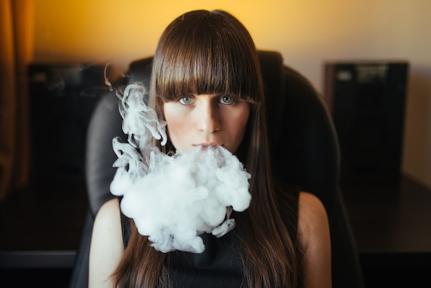 Hermosa joven exhalando humo de una pipa de agua y mirando a la cámara Foto gratis
